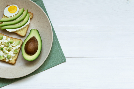 Avocado, ricotta, egg sandwiches on ceramic plate over white wooden table, top view, copy space