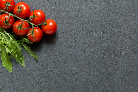 Fresh cherry tomatoes with arugula on dark stone table top view, vegetable background copy space