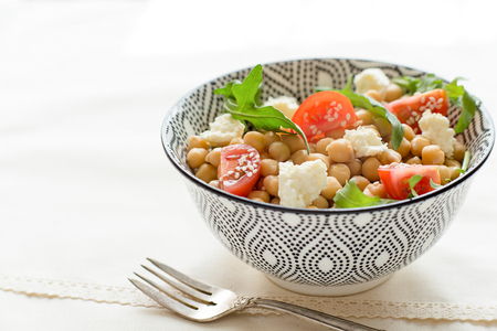 Delicious chickpeas salad on a plate, healthy vegetarian food, close up