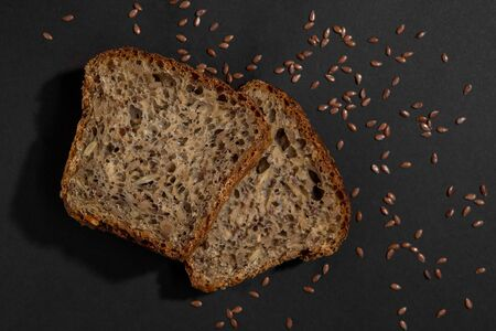 slices of brown healthy multi grain bread close up isolated on black background
