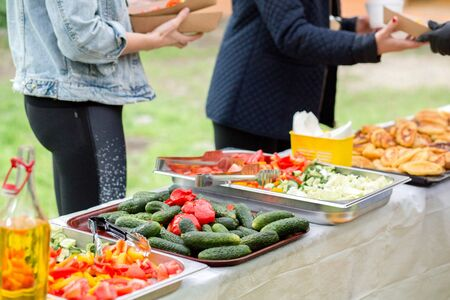 Picnic catering buffet food table vegetarian dishes, with people