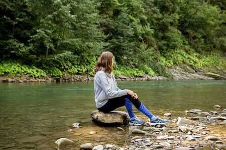 Young sports woman sitting on stone near the river and looking in the mountains, sports consept