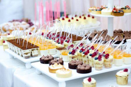 甘いデザートテーブルやキャンディバー。結婚式のパーティーマカロン、ケーキ、ケーキポップ、クローズアップキャンディバー。