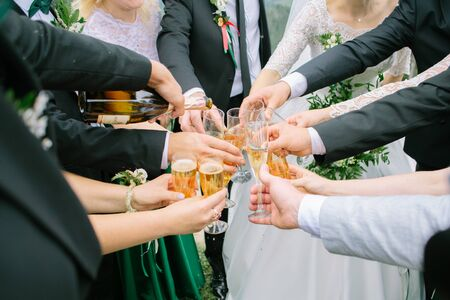 Hands of people toasting and cheering with glasses of champagne, celebrating wedding, close up