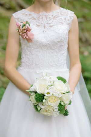 Wedding bouquet of white roses in brides hands, close up