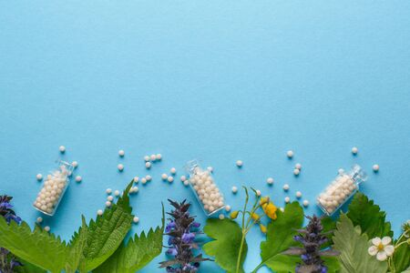 Homeopathy border background, globules in bottles and herbal on blue background. Naturopathy and alternative medicine