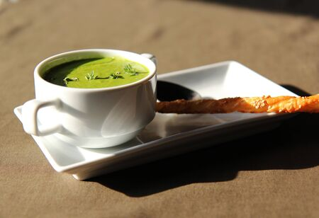 plato del bien comer: green cream soup of celery with cracker in white dishes