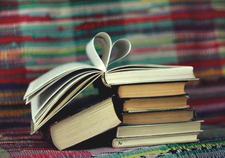 book pages: Opened book with heart shaped pages on colourful background Stock Photo