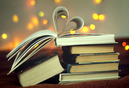 book pages: Opened book with heart shaped pages with lights glowing background Stock Photo