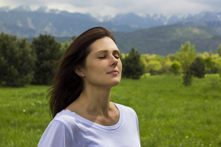 young woman with eyes closed breathing fresh air in the mountains Stock Photo