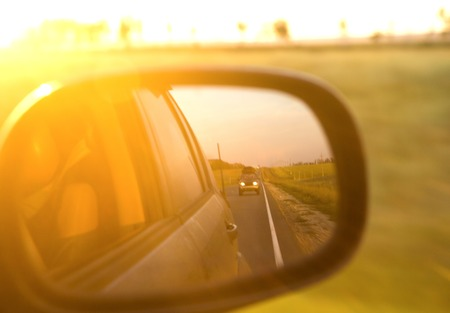 Reflection of sunny road and sunset at the car side mirrow. Banco de Imagens