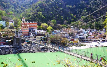 tera: RISHIKESH, INDIA - April 03, 2014 - The main view to Ganga river, bridge and temple.