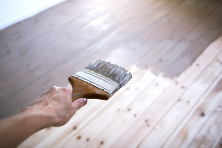 varnished: Hand painting a wooden floor with a brush. Stock Photo