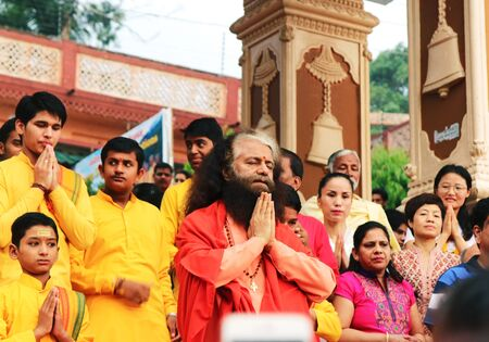 RISHIKESH, INDIA - June, 23, 2016 - Hindu students from the Parmath Niketan Ashram and tourists with guru Swami Chidanand Saraswatiji during the daily aarti prayer on the River Ganges.