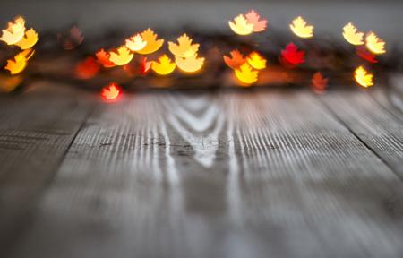 Autumn maple leaf bokeh on wooden background.