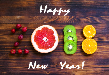 happy new year 2018 of fruit and berries on wooden background. Standard-Bild