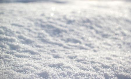 Snow background with tiny heart bokeh, winter season.