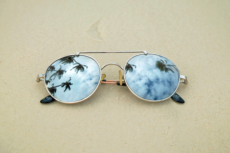 Mirrored sunglasses close up on the beach sand with palm trees reflection