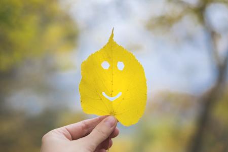 Autumn leaf emoji, smiley in a hand Stock Photo