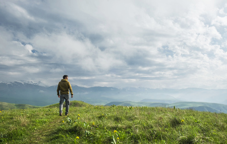 Beautiful landscape, man standing on the hill in front of mountains