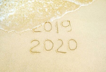 Happy new year. 2020 and 2019 written on the sand where 2019 is getting washed away by the wave.