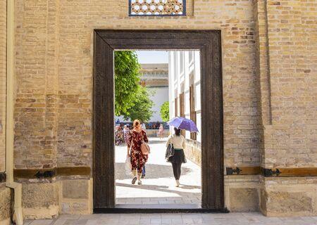 People walking through the door in memorial complex of Khoja Bahauddin Nakshband, Bukhara, Uzbekistan Reklamní fotografie