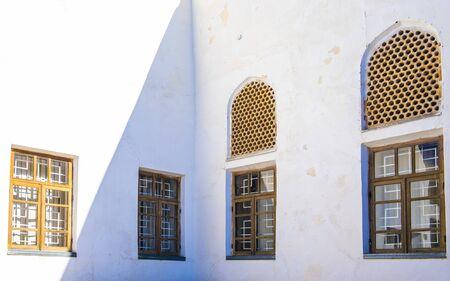 Viejas ventanas de celosía en la pared blanca en el patio interior de la antigua Arca de Bukhara, Uzbekistán.