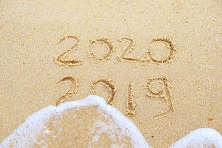 Happy new year. 2020 and 2019 written on the sand where 2019 is getting washed away by the wave