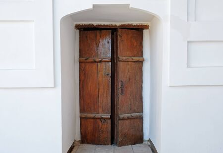 Old wooden door in the white wall.