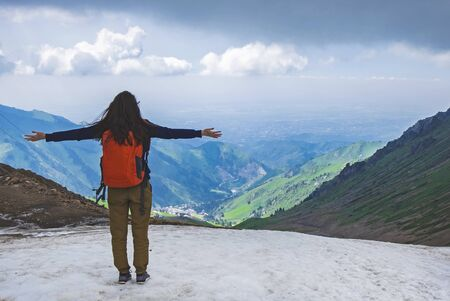 Young woman with arms outstretched standing on the mountain peak and watching beautiful landscape