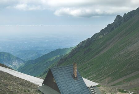 Little wooden cabin with green roof high in the mountains Stock fotó