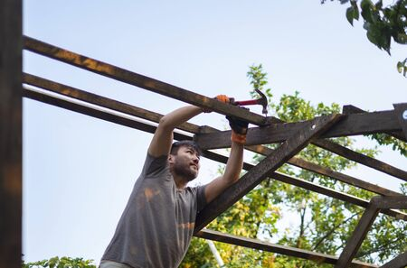 Man building wooden roof working with hammer
