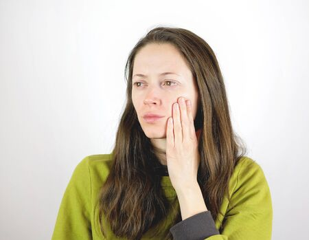 Young woman suffering from toothache, hand on the cheek, isolated on the white background Stock fotó