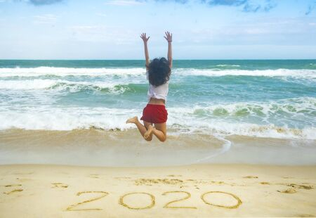 New Year 2020 on the sand, happy girl with hands up jumping on the beach Stock fotó