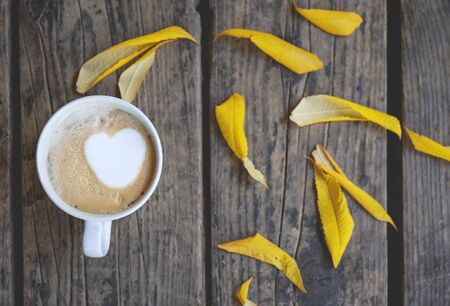 A cup of coffee with a heart in a white cup and yellow autumn leaves on the wooden background Stock fotó