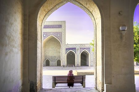 Inner yard of Kalyan Mosque, part of the Po-i-Kalyan Complex, at the sunset. Bukhara, Uzbekistan. A woman in a headscarf sitting on the bench. Stock Photo