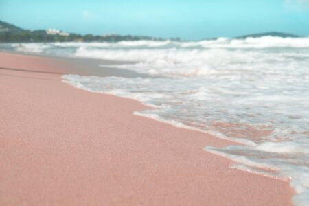Pink and blue colours, waves on the sand beach