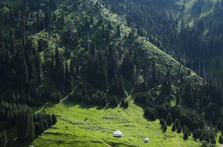 Beautiful view to the high green mountains and white kazakh national yurts, Almaty, Kazakhstan