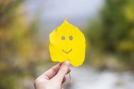 Autumn leaf smiling face in a hand