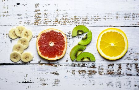 New year 2020 made of fruit on white wooden background.