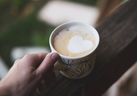 A cup of coffee with a heart in a white cup in a hand.
