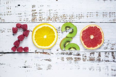 New year 2020 made of fruit and berries on white wooden background Stock fotó