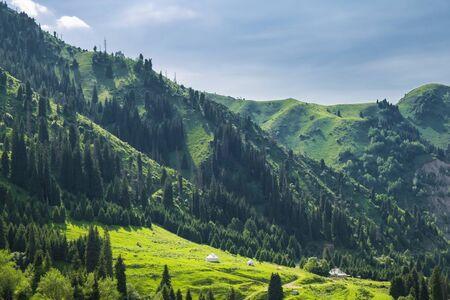 Beautiful view to the high green mountains and white kazakh national yurts, Almaty, Kazakhstan.