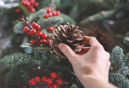 making christmas wreath with fir tree branches and decorations. Cone in a hand.