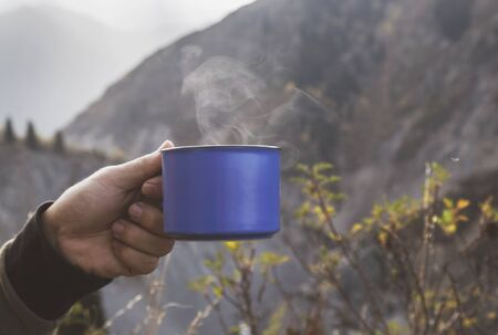 female hand with a cup of coffee on the mountain lake background. Stock fotó
