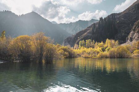 Beautiful autumn landscape. Mountains and lake, yellow trees in the reflection. Almaty, Kazakhstan. Stock fotó