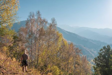 Man walking in beautiful autumn mountains. Almaty, Kazakhstan.