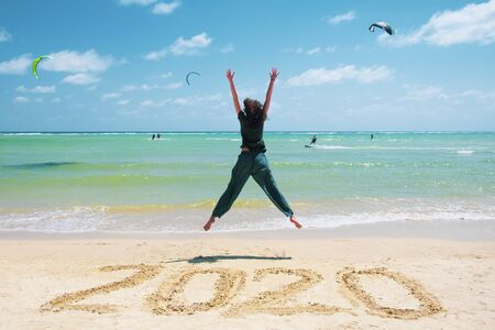 New Year 2020 on the sand,happy girl with hands up jumping on the beach.