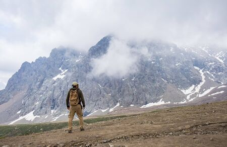 Rear view of man standing at the foot of impressive mountain. Kazakhstan, Almaty.
