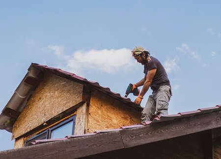 Man working on roof using electric screwdriver
